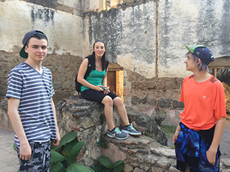 students on field trip in Guatemala - sitting on rubble wall