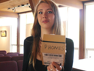 "Student showing off box marked ""Phones"""