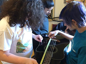 Students learning music with a guitar